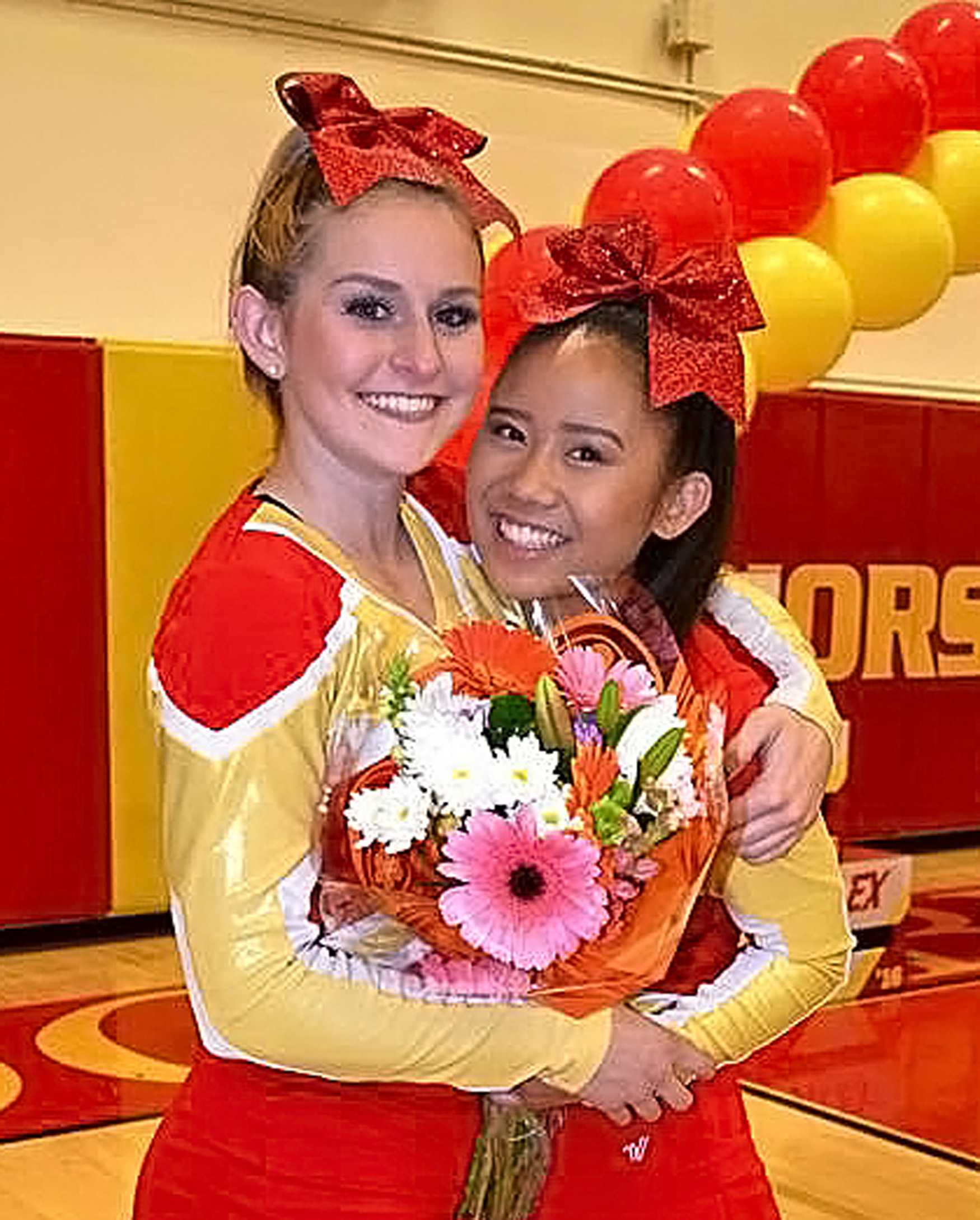 Senior Kayla Bunnell and sophomore Danielle Lee warmly embrace each other after the closing of the cheer showcase