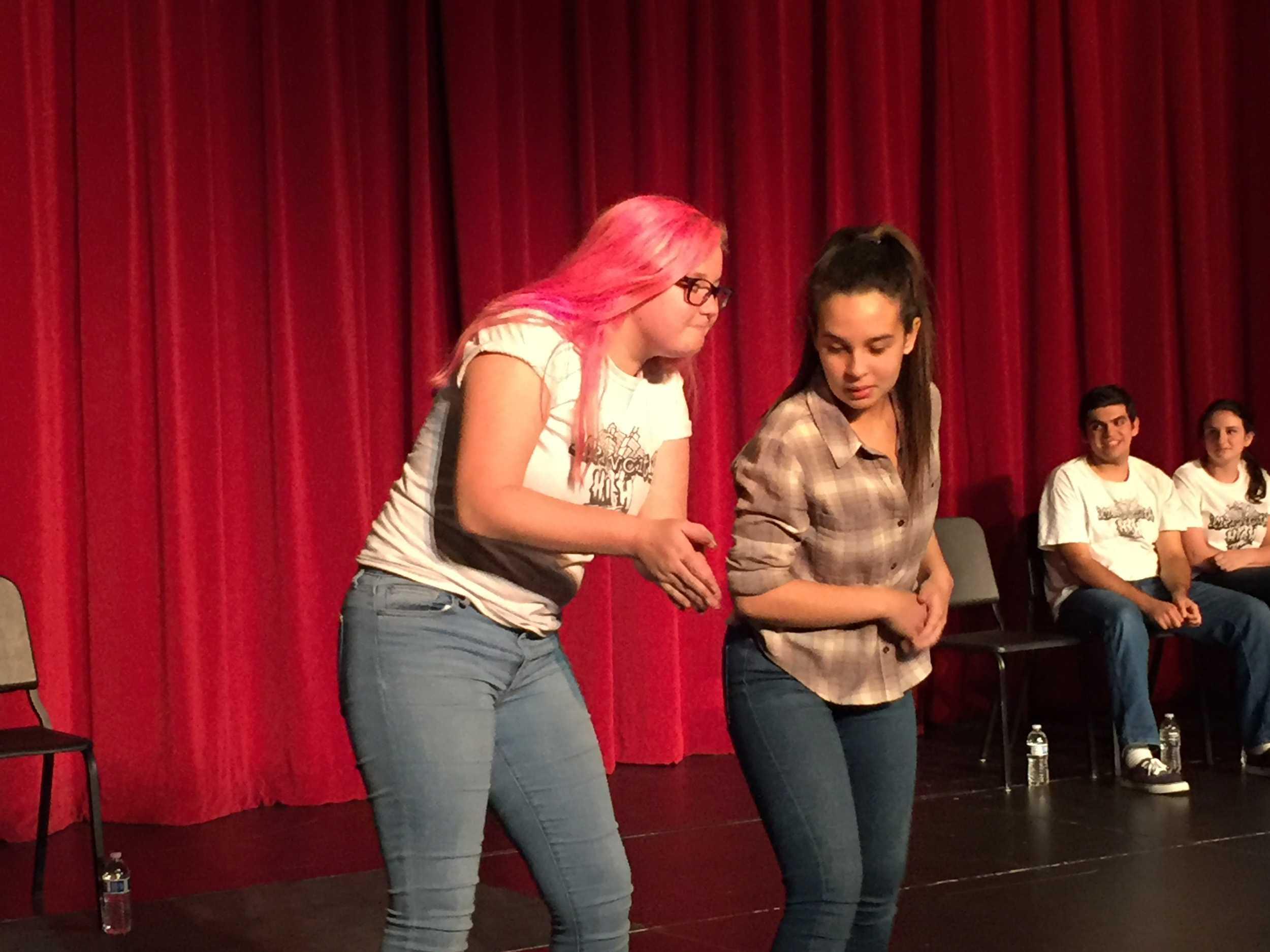 Alumni Gabi Feliciano and junior Rowan Biggs help fill the theater with laughter.