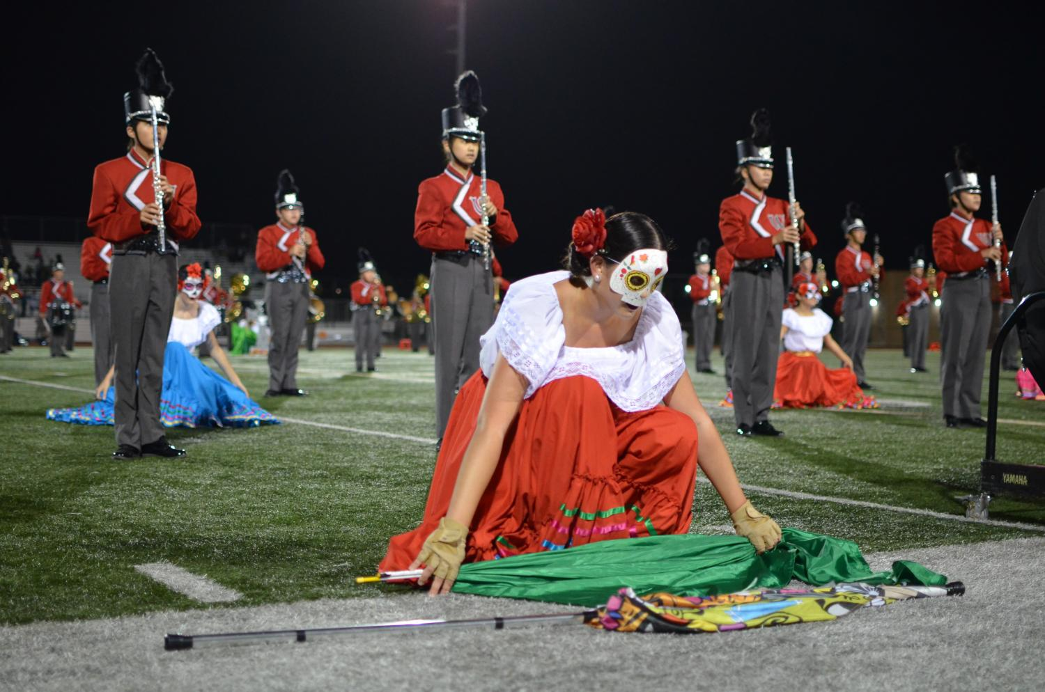 Colorguard performer, Alexis Chirco, senior, sets down her flag and takes a deep breath as she begins the next segment of the halftime show.