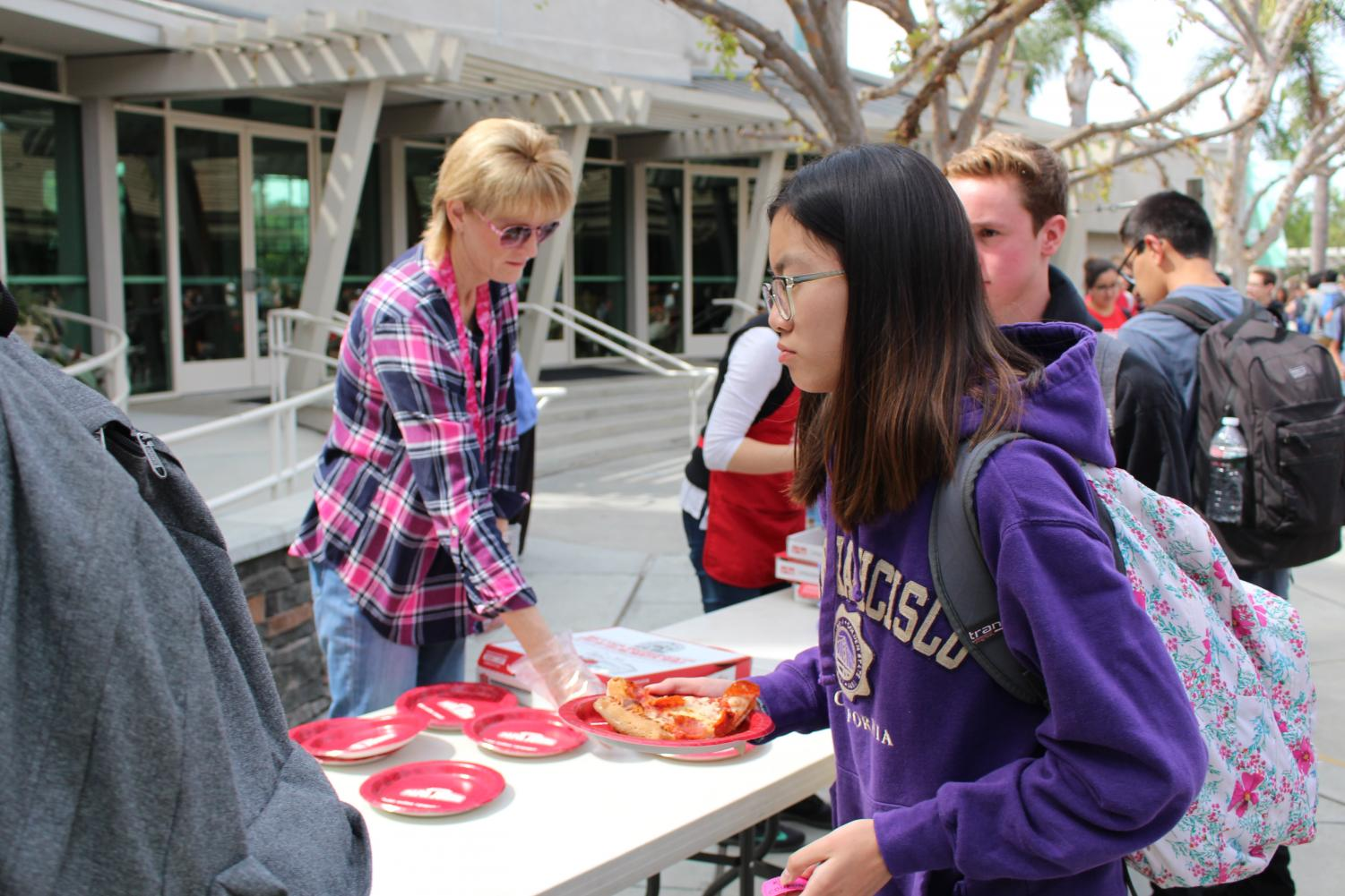 """Pizza Friday"" staff members hand out tickets and pass out pizza to students."