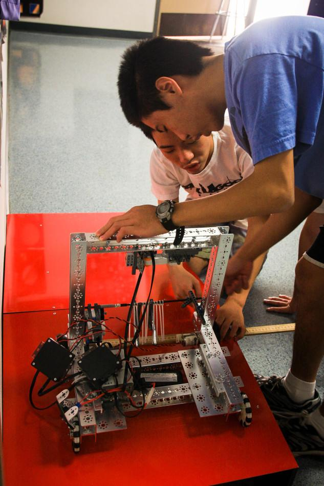 Juniors Benjamin and Jonathan Fong work on fixing the robot that is being built for the First Tech Challenge.
