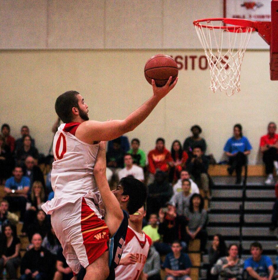 Senior Ajdin Toskic leaps for a layup at the Woodbridge Gym during a game against University High.