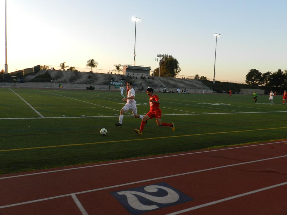 Senior Kevin Pineda (right) runs down the line, dribbling the ball past an Irvine defender.