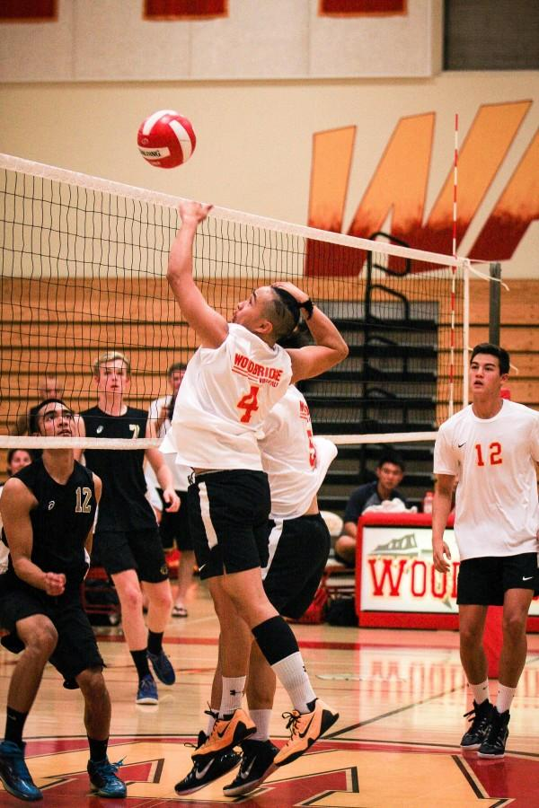 Senior+Josh+Bright+leaps+up+to+spike+the+ball+over+the+net.