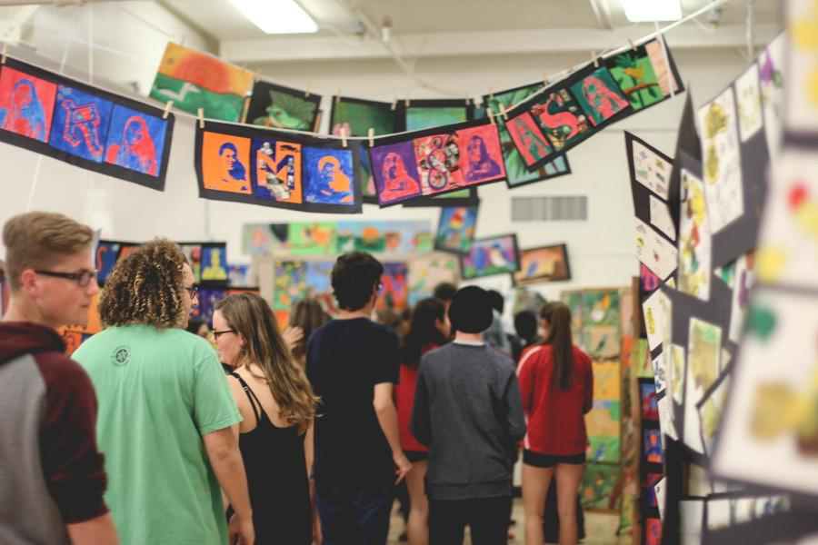 Students explore the upper gym, which was transformed into a student art gallery for Fine Arts Day.