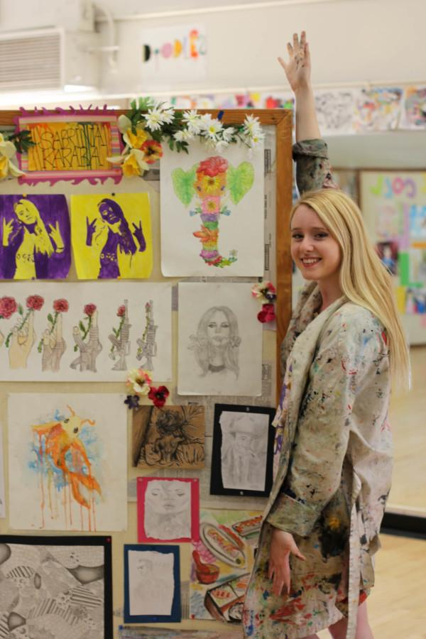 Karaba poses next to her art on display.