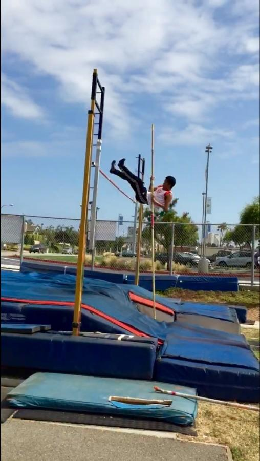 Senior Calvin Tran pushes himself up and over the bar while pole vaulting.