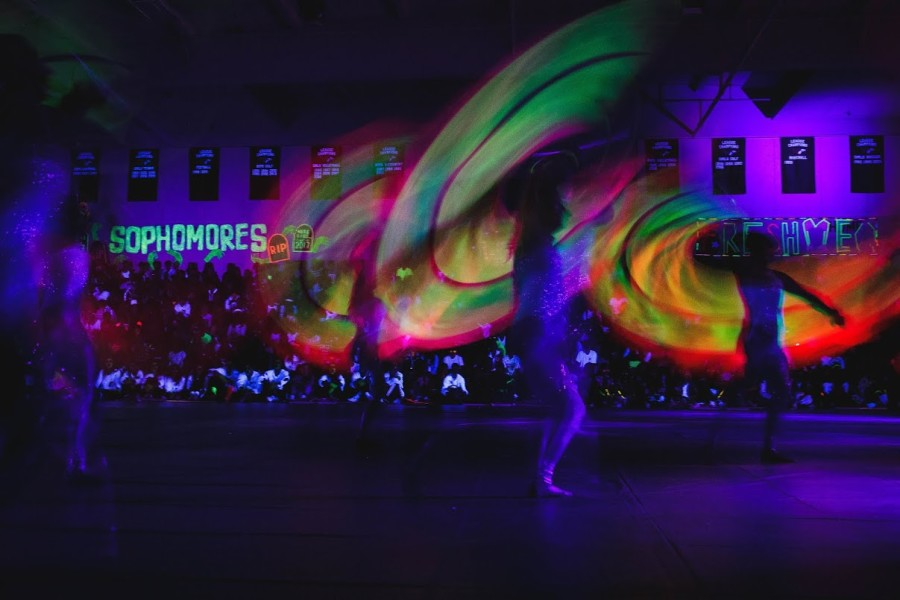 Colorguard uses glow-in-the-dark flags under a black light during their performance at the pep rally.