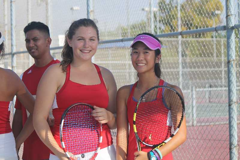 Senior Nicole Dostanic and junior Claire Dean pose with their rackets after their win against Irvine High