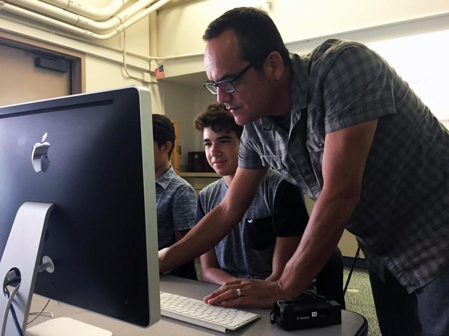 Digital Media teacher helps his students to edit photos and videos