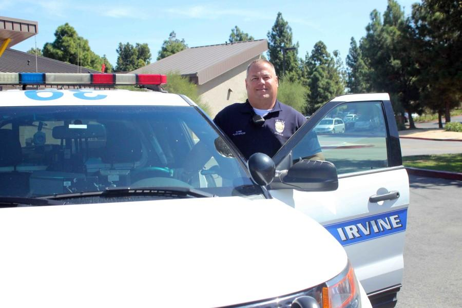 Officer Frei stands next to his police car in the parking lot