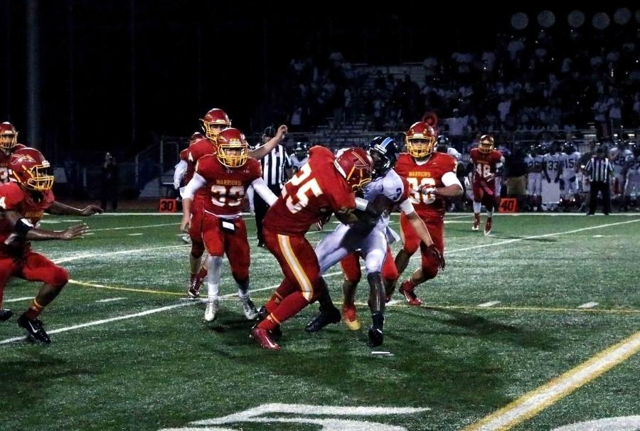 Warriors stop Irvine football player during the second half of the Homecoming game at Uni High Stadium