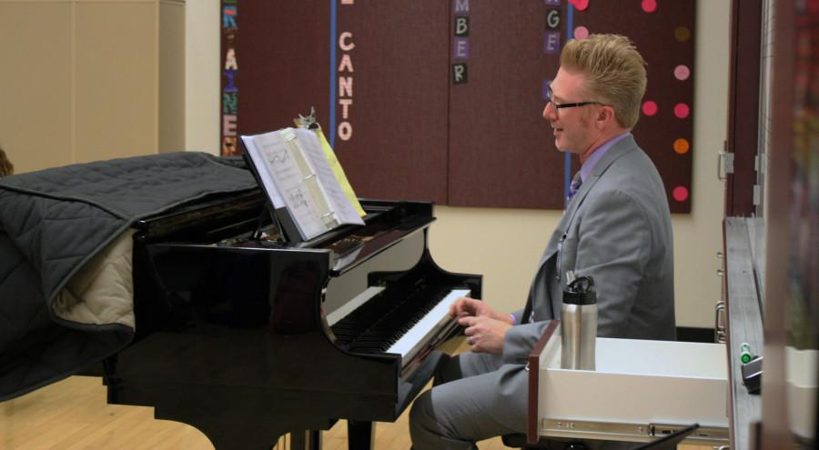Vocal teacher Rob Blaney directs rehearsal while accompanying on the piano.