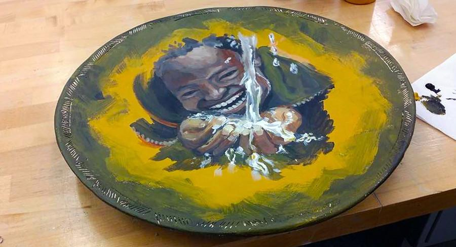 A child's face is painted on a bowl for auction by Amy Park.
