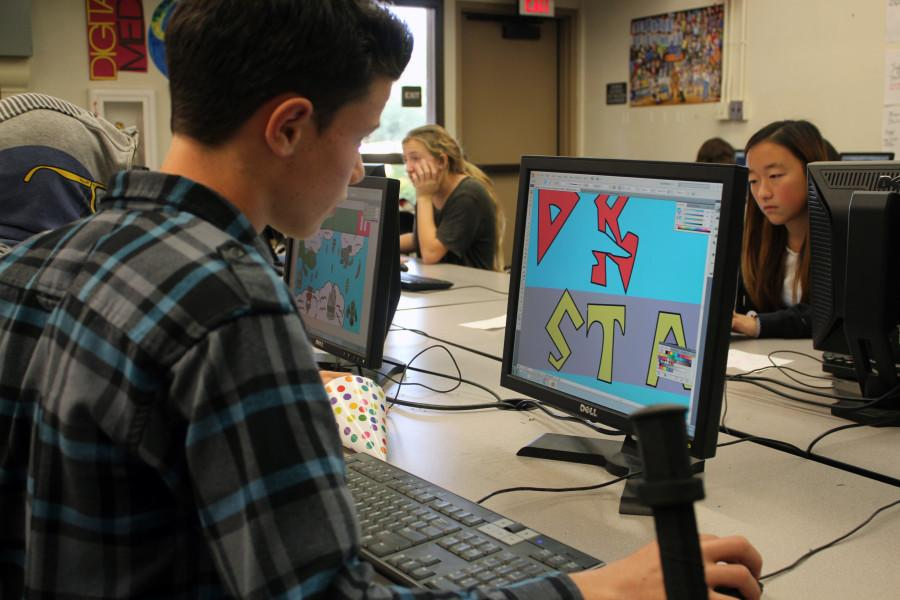 Students work vivaciously on media designs on their computers