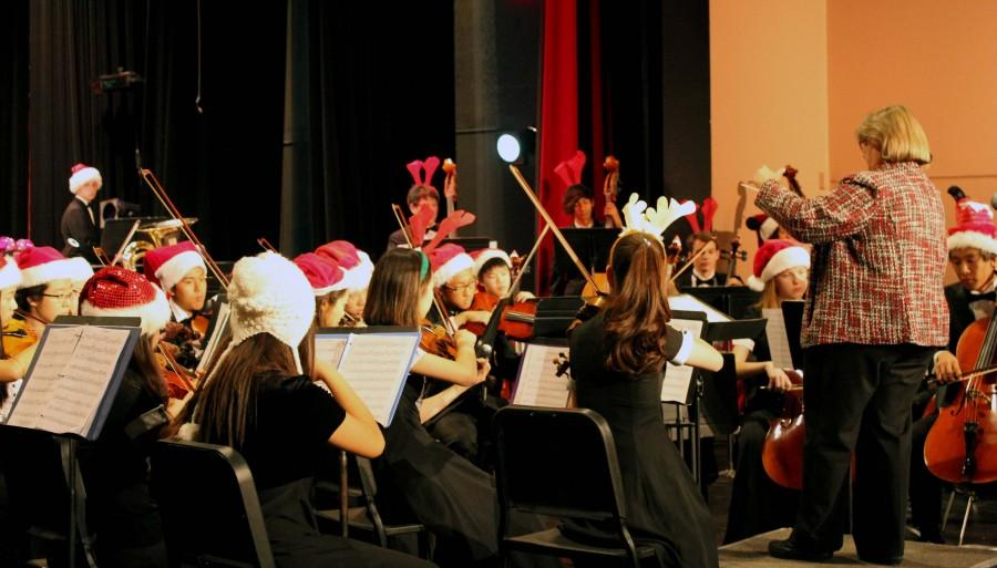 Students, in Santa hats, perform energetic pieces for their audience.