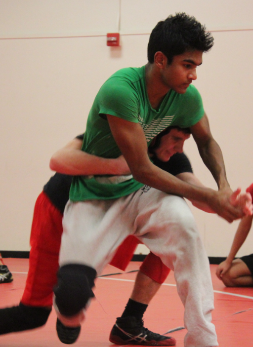 Juniors captains Neil Naraj and Liam MacArthur demonstrate a body lock to their teammates in order to prepare for upcoming matches against Northwood High and Beckman High.