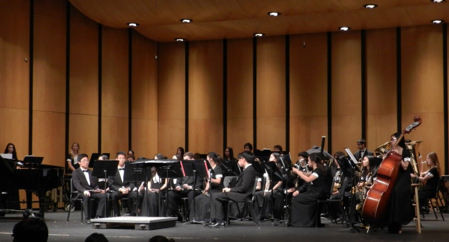 Wind ensemble members take their places as an administrator introduces the piece,