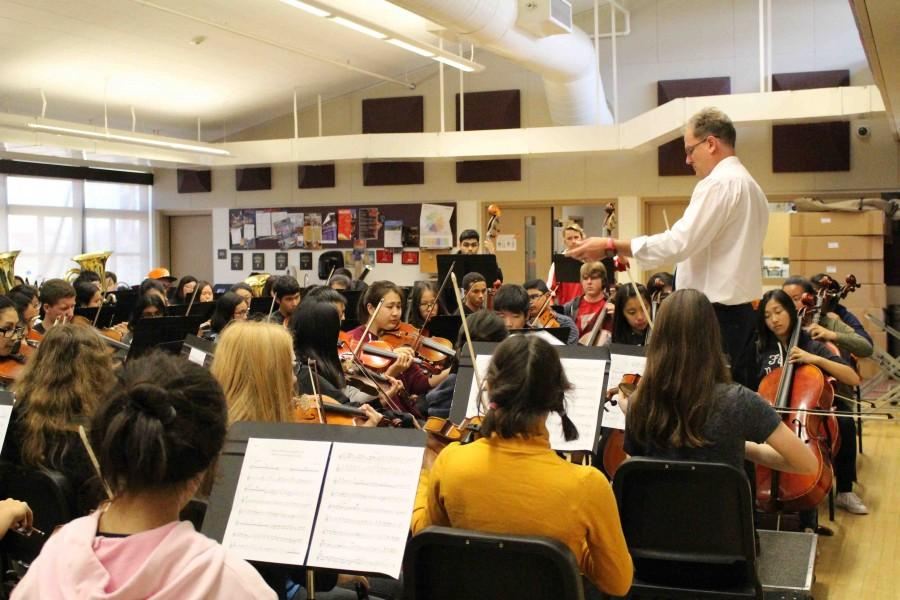 Music+teachers+Brad+Harris+conducts+Symphonic+Orchestra%2C+setting+the+tempo+of+the+piece+as+students+follow+his+lead.+
