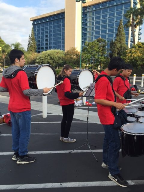 Seniors Kat Canellos and Gabriel Vivanco and juniors Sun Jae Woo and Shane Park practice in the parking lot as they prepare to march into Disneyland
