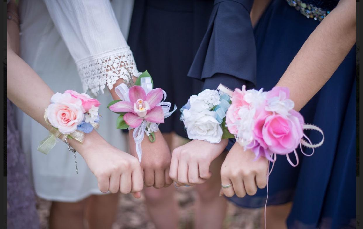 A group of students who went to Winter Formal posed for a picture with their corsages as a part of Winter Formal tradition.