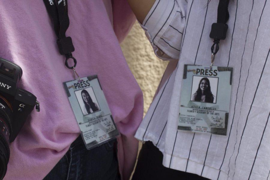 Seniors Bianca Gomez and Atria Jamshidi pose with their name tags and cameras.