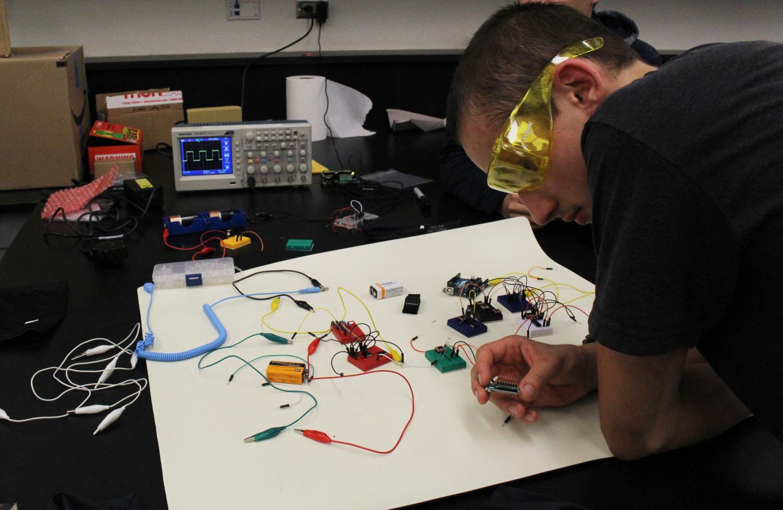 Sophomore Daniel Vasenko examines one of the crucial parts of the satellite.