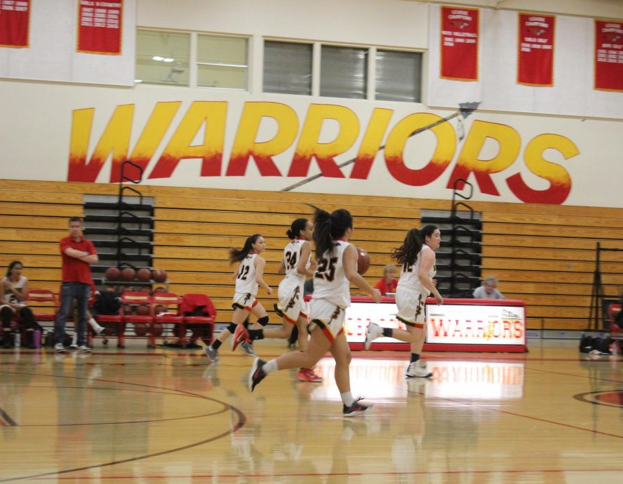 Warriors dribble down the court with possession o the ball