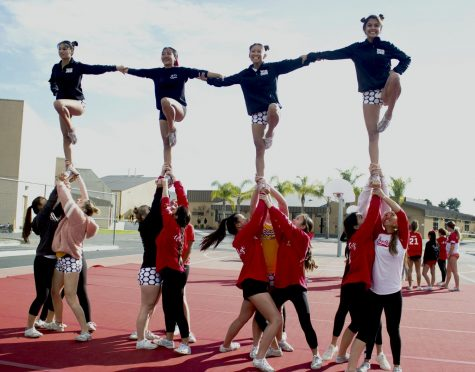 WHS cheerleaders lift up their teammates into the air while performing a stunt.