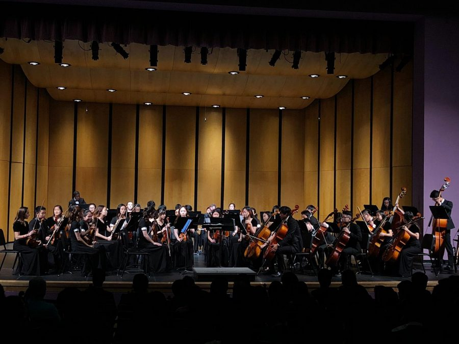 Students perform a composed piece in the spacious auditorium.