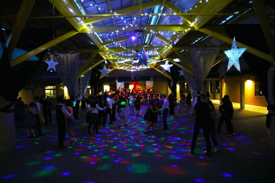 Attendees dance the night away in the dark night illuminated by intricate lighting in the music quad.