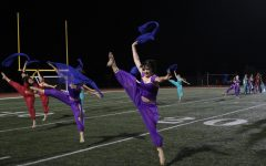 Dancers leap across the field to the marching band tunes.