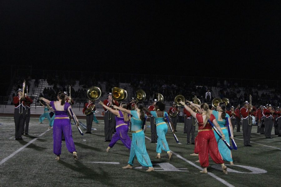 Musicians and dancers blend to form a diverse performance in the center of the football field.
