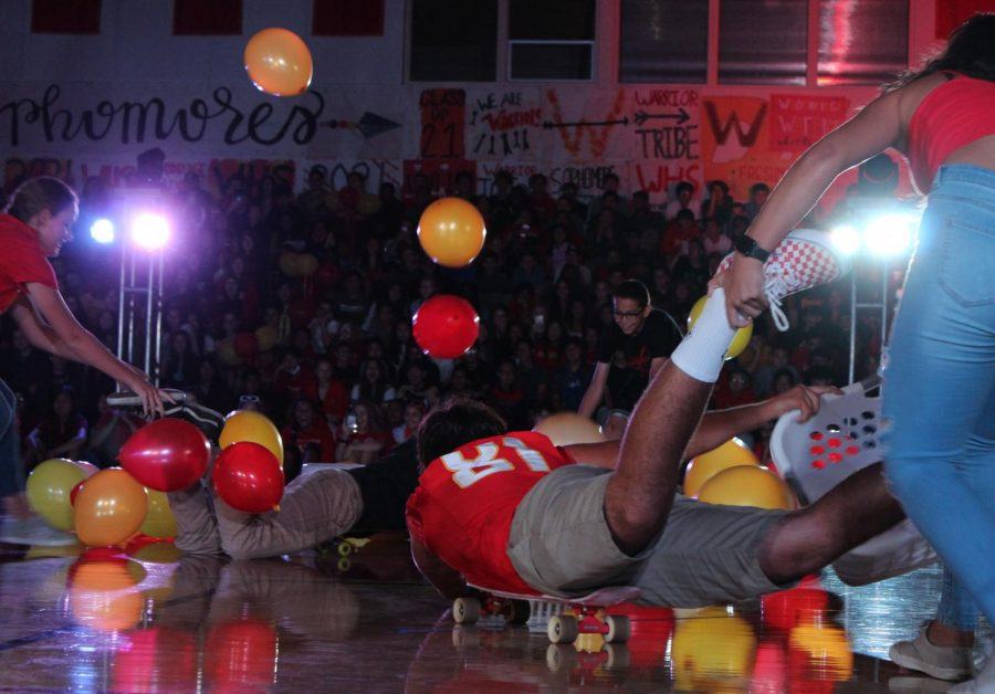 Students from different classes passionately compete to collect the most balloons in the pep rally game.
