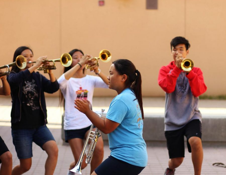 Junior+and+trumpet+section+leader+Justine+Sato+guides+her+classmates+through+a+trumpet+routine.