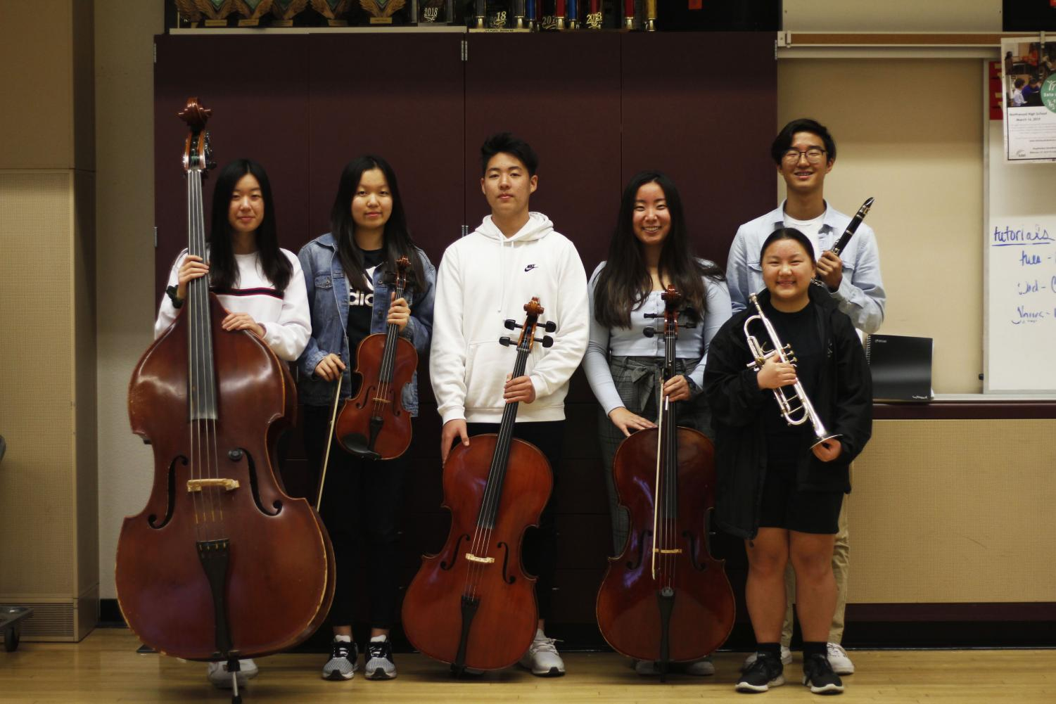 Juniors Megan Lu, Claire Kim, Eric Kim, Allison Hu, Justine Sato and Jay Hong pose with their instruments