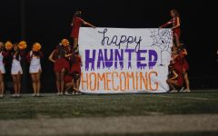 The cheerleaders present the Haunted Homecoming Football sign for all to see.