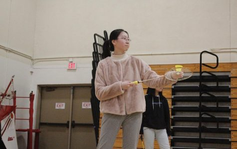 Junior and badminton player Julia Yuan prepares to serve the badminton shuttlecock.